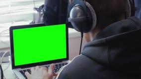 Mens in hoofdtelefoons met het groen scherm stock videobeelden