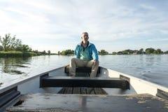Mens in houten boot op het meer royalty-vrije stock afbeeldingen