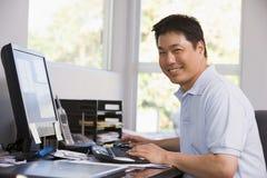 Mens in huisbureau dat computer en het glimlachen gebruikt royalty-vrije stock afbeelding