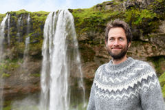 Mens in Ijslandse sweater door waterval op IJsland Stock Foto