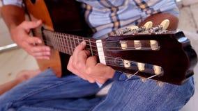 Mens in jeans en controleoverhemd het spelen gitaar stock footage