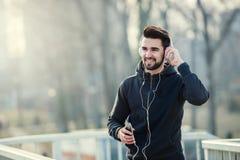 Mens Jogger met Hoofdtelefoons die Smartphone en het Luisteren Muziek gebruiken Stock Fotografie