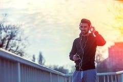 Mens Jogger met Hoofdtelefoons die Smartphone en het Luisteren Muziek gebruiken Royalty-vrije Stock Afbeeldingen