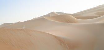 Mens in kandura in een woestijn bij zonsopgang Stock Foto's