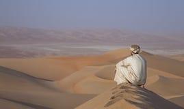 Mens in kandura in een woestijn bij zonsopgang Royalty-vrije Stock Fotografie