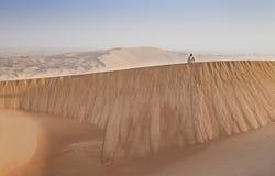 Mens in kandura in een woestijn bij zonsopgang Royalty-vrije Stock Foto