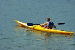 Mens kayakin royalty-vrije stock afbeeldingen