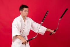 Mens in kimono het praktizeren vechtsporten Hoofdkata van vertoningsnunchaku Stock Foto