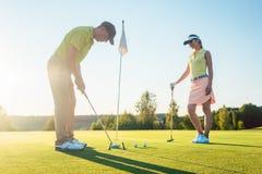 Mens klaar om de golfbal te raken terwijl het uitoefenen met zijn spelpartner royalty-vrije stock afbeelding