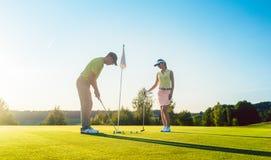 Mens klaar om de golfbal te raken terwijl het uitoefenen met zijn spelpartner stock afbeelding