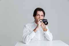Mens klaar om foto te maken terwijl het zitten bij de lijst Royalty-vrije Stock Foto's