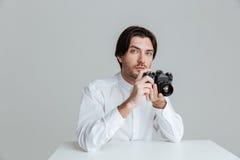 Mens klaar om foto te maken terwijl het zitten bij de lijst Royalty-vrije Stock Foto