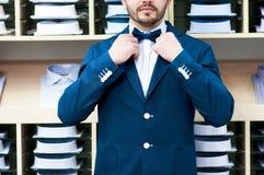 Mens in klassiek kostuum tegen showcase met overhemden Royalty-vrije Stock Afbeelding