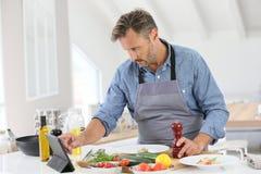 Mens koken het op middelbare leeftijd in de keuken royalty-vrije stock foto