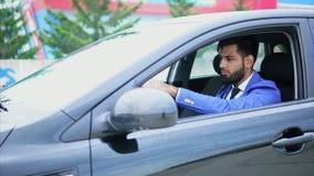 Mens in kostuum die de auto drijven Moslimmens met ernstig gezicht die linkerauto drijven stock videobeelden