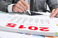 Mens in kostuum die een tablet en een kalender van 2015 gebruiken Royalty-vrije Stock Foto's