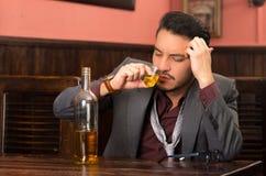 Mens in kostuum het drinken alcoholschot stock foto