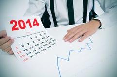 Mens in kostuum met een grafiek en een kalender van 2014 Royalty-vrije Stock Afbeeldingen