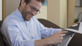 Mens in krant lezen en oogglazen die, ochtendritueel, vrije tijd glimlachen stock footage