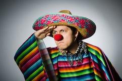 Mens in levendige Mexicaanse poncho tegen grijs Stock Afbeeldingen