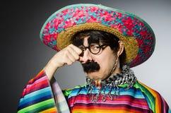 Mens in levendige Mexicaanse poncho tegen grijs Stock Foto's
