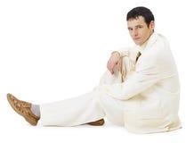 Mens in licht pak dat op wit situeert Royalty-vrije Stock Afbeeldingen