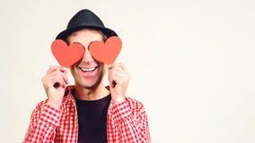 Mens in liefde De gelukkige mens behandelde zijn ogen door rode die harten, op wit worden geïsoleerd De ruimte van het exemplaar  royalty-vrije stock foto
