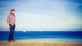 Mens lopen ontspannen op steenmuur door kust stock fotografie