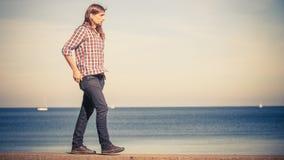 Mens lopen ontspannen op steenmuur door kust stock foto