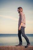 Mens lopen ontspannen op steenmuur door kust royalty-vrije stock fotografie
