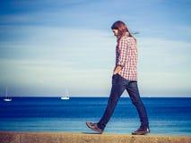 Mens lopen ontspannen op steenmuur door kust stock foto's
