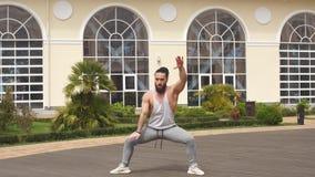 Mens met baard die hurkzit doen die in openlucht het tonen van macht en sterkte opleiden stock video
