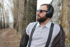 Mens met baard en hoofdtelefoons in het park Stock Fotografie