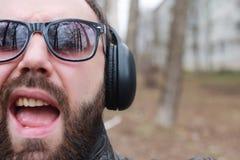 Mens met baard en hoofdtelefoons in het park Royalty-vrije Stock Foto
