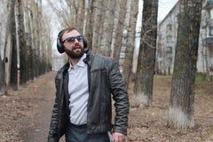 Mens met baard en hoofdtelefoons in park Stock Afbeeldingen