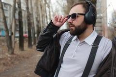 Mens met baard en hoofdtelefoons in park Stock Foto