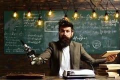 Mens met baard en snor op universiteit Gebaarde mens met boek en retro schrijfmachine De wetenschapper maakt onderzoek met royalty-vrije stock foto