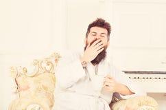 Mens met baard en snorgeeuwen terwijl het zitten op ouderwetse luxeleunstoel De mens slaperig in badjas drinkt koffie royalty-vrije stock fotografie