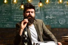 Mens met baard op het denken gezicht Gebaarde mens met retro schrijfmachine en microscoop De wetenschapper maakt onderzoek op uni stock foto