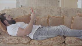 Mens met baard op zachte beige bank op midden van de dag die en sms of iets zoeken in Internet ontspannen typen stock videobeelden