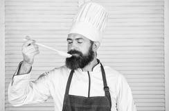 Mens met baard in van de kokhoed en schort greep kokende hulpmiddelen Het koken als professionele activiteit Greep van de Hipster royalty-vrije stock foto's