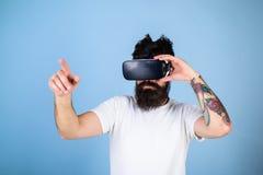 Mens met baard in VR-glazen, lichtblauwe achtergrond Interactief oppervlakteconcept Hipster bij het bezige gezicht virtueel onder royalty-vrije stock afbeelding