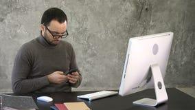 Mens met baard, zit hij bij een zwarte lijst, bekijkend zijn smartphone met zijn computer voor hem stock video
