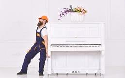 Mens met baardarbeider in helm en overallduwen, inspanningen om piano, witte achtergrond te bewegen De koerier levert meubilair stock foto's