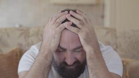 Mens met baardzitting op de bank op het midden van de dag en het nemen van zijn hoofd wegens vreselijke hoofdpijn stock footage