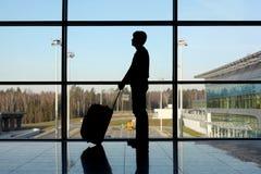 Mens met bagage die zich dichtbij venster in luchthaven bevindt Stock Afbeelding