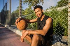 Mens met bal op basketbalhof speler die aan de camera op een basketbalhof kijken Stock Foto's