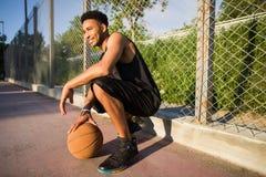 Mens met bal op basketbalhof speler die aan de camera op een basketbalhof kijken Royalty-vrije Stock Afbeelding
