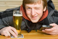 Mens met bier en palm-grootte computer Stock Afbeelding