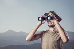 Mens met binoculair in de bergen Royalty-vrije Stock Afbeeldingen